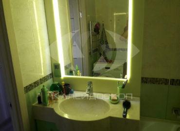 Столешница из акрилового камня с раковиной подстольного монтажа и зеркалом в рамке из камня.