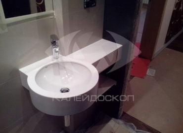 Столешница для ванной из белого акрилового камня с выдвинутой вперед круглой раковиной интегрированной в столешницу.